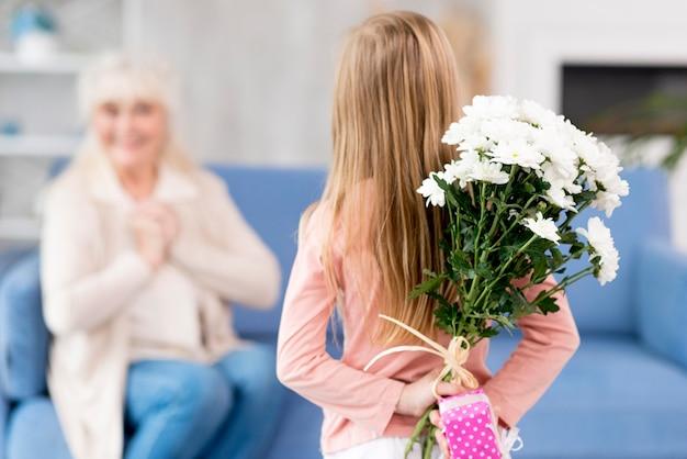 Meisje verrassende oma met bloemen
