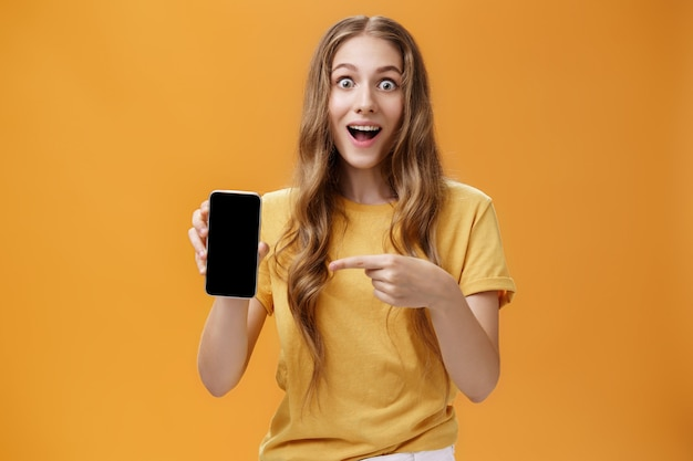 Meisje verrast met geweldige smartphonefuncties. portret van opgetogen en verbaasde schattige europese slanke vrouw met golvend natuurlijk kapsel met mobiele telefoon wijzend op gadgetscherm op app. ruimte kopiëren