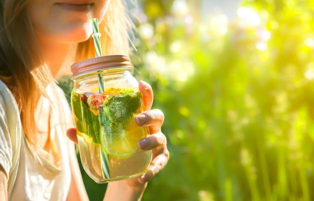 Meisje verse limonade drinken in potten met rietjes. hipster zomerdrankjes. milieuvriendelijk in de natuur. citroenen, sinaasappelen en bessen met munt in het glas.