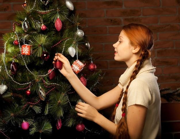 Meisje versier de kerstboom in het interieur van een huis