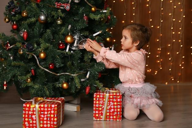 Meisje versieren de kerstboom in een huis interieur.