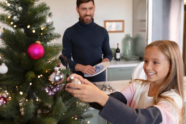 Meisje versiert de kerstboom terwijl haar vader de afwas doet