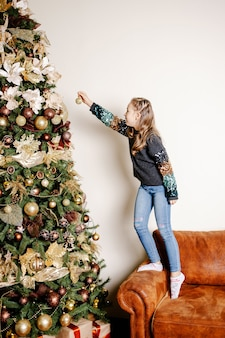 Meisje versiert een kerstboom. mooi meisje dat gouden kerstmisstuk speelgoed houdt.