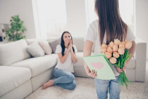 Meisje verstopt achter rug verjaardagscadeau briefkaart tulpen bloemen voor moeder binnenshuis binnenshuis