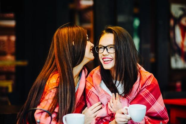 Meisje vertelt een geheim aan een ander meisje bedekt een deken