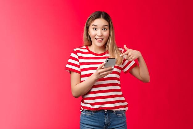 Meisje vertelt je over geweldige promo online winkel glimlachend onder de indruk houd smartphone wijzende vinger p...