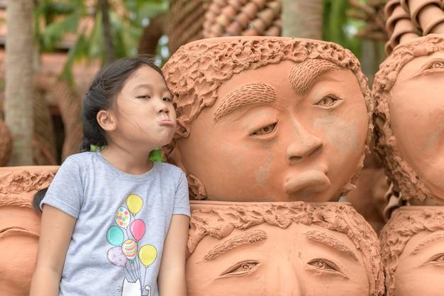 Meisje verveeld of boos emotie tonen in de buurt van klei potten,
