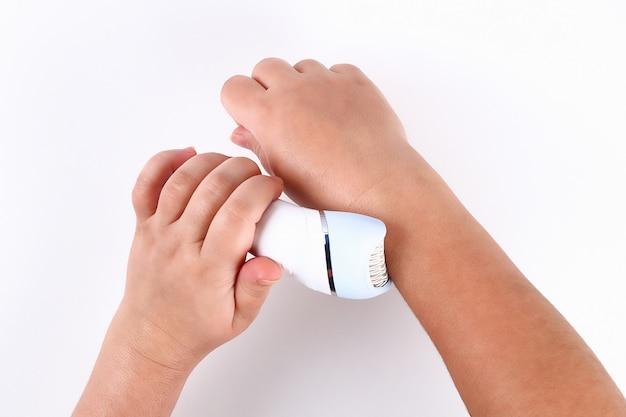 Meisje verwijdert haar met elektrische epilator in haar handen