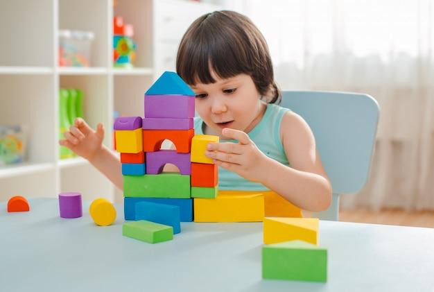 Meisje verzamelt een houten ongeverfde piramide. veilig natuurlijk houten kinderspeelgoed.