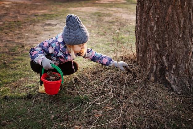 Meisje verzamelt hobbels tijdens een wandeling in het bos