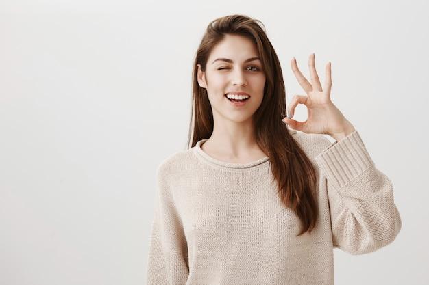 Meisje verzekert en beveelt product aan, knipoogt en toont een goed gebaar om kwaliteit te garanderen