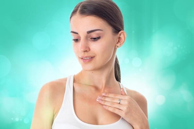 Meisje verzorgt haar huid met crème geïsoleerd op een witte achtergrond. gezondheidszorgconcept. lichaamsverzorgingsconcept. jonge vrouw met een gezonde huid.