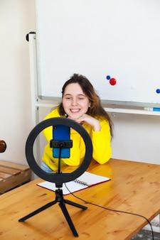 Meisje video-opname op smartphone en zichzelf verlicht met ringlamp
