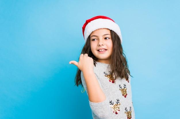 Meisje vieren kerstdag punten met duim vinger weg, lachen en zorgeloos.