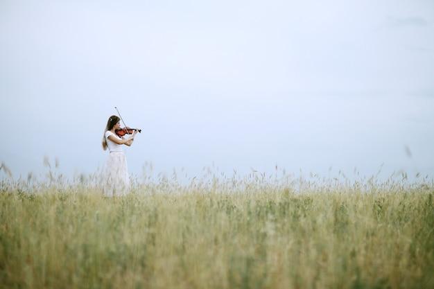 Meisje viool spelen in het veld