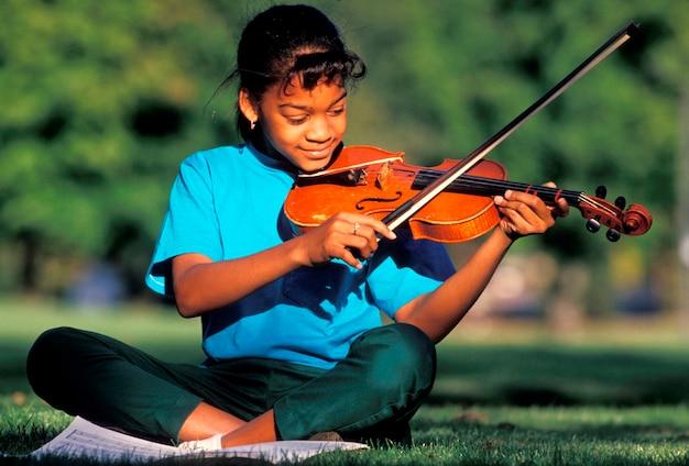 Meisje viool spelen in park