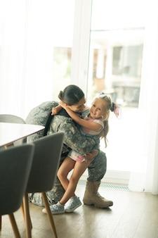Meisje voelt zich geweldig. grappig blond meisje dat zich geweldig voelt terwijl ze haar moeder in de strijdkrachten thuis ziet dienen