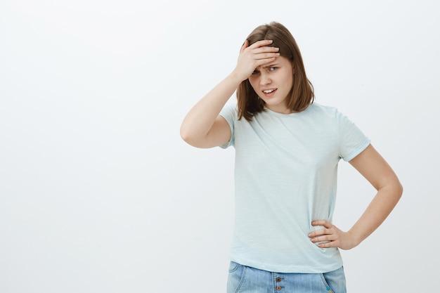 Meisje voelt zich vernederd als ze moeder ziet in de buurt van de universiteit. onhandige, ontevreden en beschaamde schattige jonge vrouw in t-shirt die gezicht bedekt met handpalm op voorhoofd van onder voorhoofd kijken ontevreden