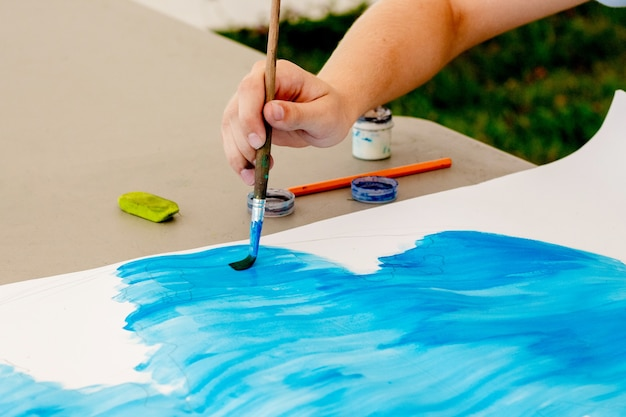 Meisje voert tekening op papier blauwe verf. meisje houdt een penseel in haar hand tijdens het tekenen