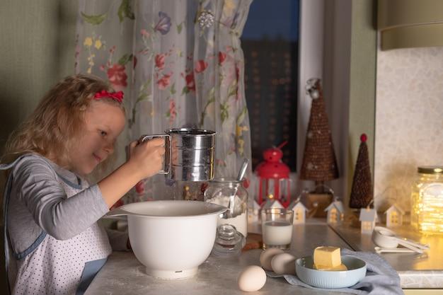 Meisje voorbereiding deeg in kom tegen kerstversiering