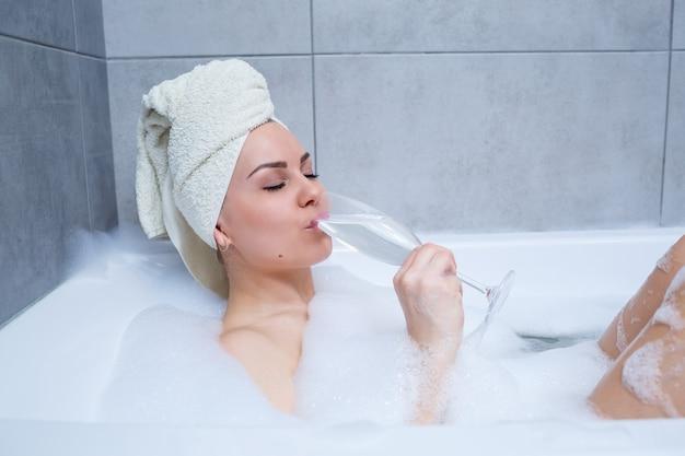 Meisje vrouw met een witte handdoek op haar hoofd ligt met een glas champagne in een witte badkuip. in haar handen veel plaszeep. volledig whirlpoolschuim. ontspan na een zware dag. ontspanningsprocedure in de spa