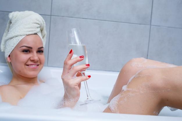 Meisje vrouw met een witte handdoek op haar hoofd ligt met een glas champagne in een witte badkuip. in haar handen veel plaszeep. volledig whirlpoolschuim. ontspan na een zware dag. spa ontspannende procedure