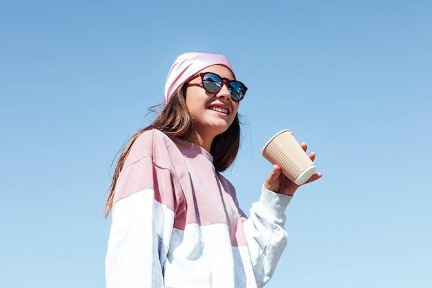 Meisje vrouw met zonnebril en een roze hoofddoek op haar hoofd, drinkt een kopje koffie. internationale borstkankerdag, met de lucht op de achtergrond.