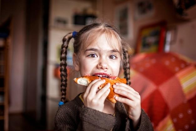 Meisje vuil met bessenjam eten zelfgemaakte pasteitje, indoor emotionele levensstijl portret