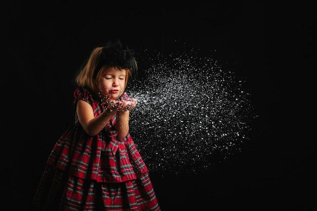 Meisje waait de sneeuw uit haar handen