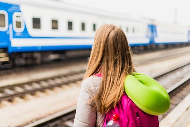 Meisje wacht op de trein. meisje met een rugzak en met groene nek kussen