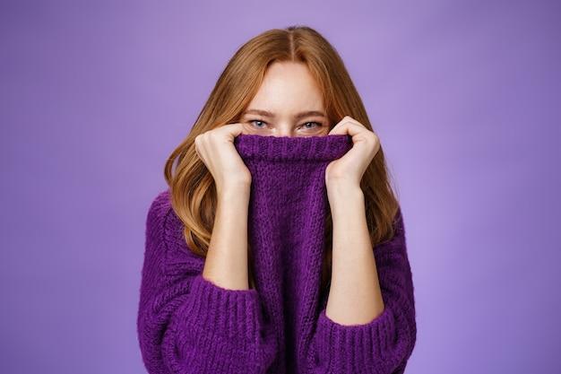 Meisje wacht op de winter met een vrolijke grijns die klaar is om op te warmen met een gezellige trui die de kraag op het gezicht trekt en lacht met de ogen naar de camera die positief en schattig staat tegen een paarse achtergrond.