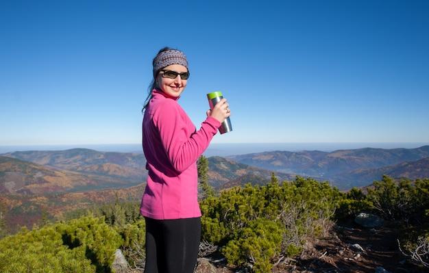 Meisje wandelaar bereikte de bergtop, genietend van haar rust en glimlachen
