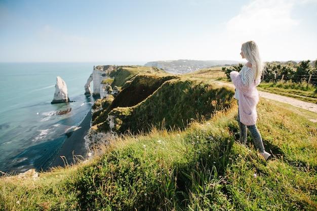 Meisje wandelen en het nemen van foto van de kliffen van etretat en de atlantische oceaan in etretat, frankrijk