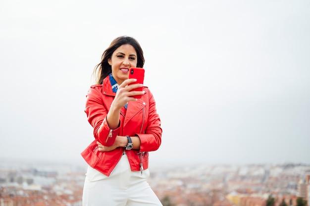 Meisje wandelen en sms'en op rode smartphone met stad op achtergrond