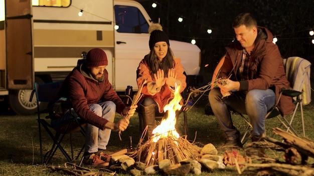 Meisje warmt haar handen op terwijl haar vriend het vuur sterker maakt. kamp vuur. retro camper. gloeilampen.