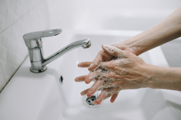 Meisje wast haar handen grondig met zeep onder water in een witte badkamer conceptuele foto van reinheid