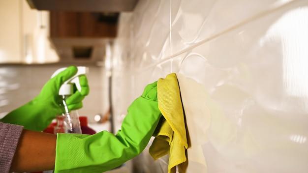Meisje wast tegels in de keuken.