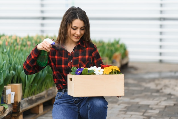 Meisje, werknemer met bloemen in kas
