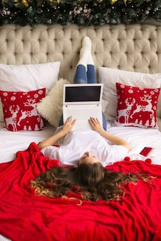 Meisje werkt online, vanuit huis, ligt op bed, videoverbinding