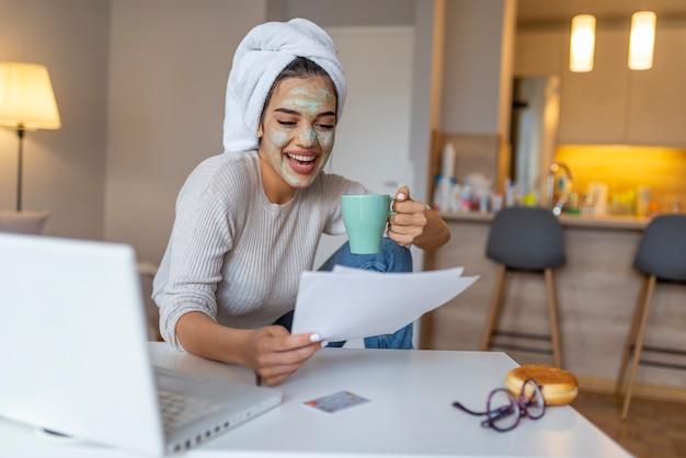 Meisje werkt vanuit huis, ze heeft een gezichtsmasker en ze is in de badjas.
