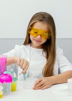 Meisje wetenschapper met veiligheidsbril plezier maken van slijm in het lab
