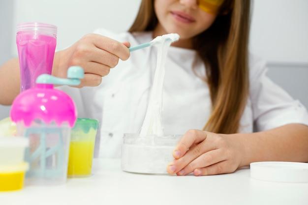 Meisje wetenschapper met veiligheidsbril plezier maken van slijm in het laboratorium