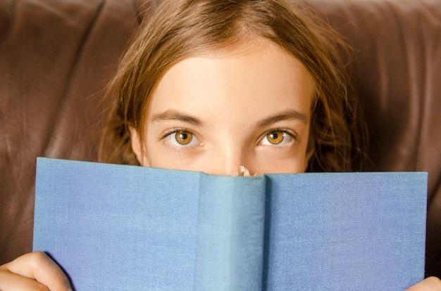 Meisje wijd open ogen boven open blauwe boekdekking. verrast klein kind tijdens het lezen van een boek