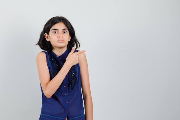 Meisje wijst naar de kant in blauwe blouse en kijkt verbaasd