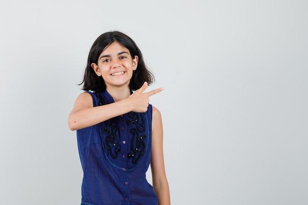 Meisje wijst naar de kant in blauwe blouse en kijkt vrolijk