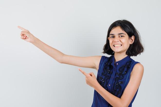 Meisje wijst naar de linkerbovenhoek in blauwe blouse en kijkt joviaal.
