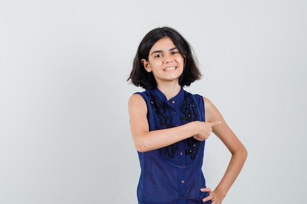 Meisje wijst naar de rechterkant in blauwe blouse en kijkt vrolijk.