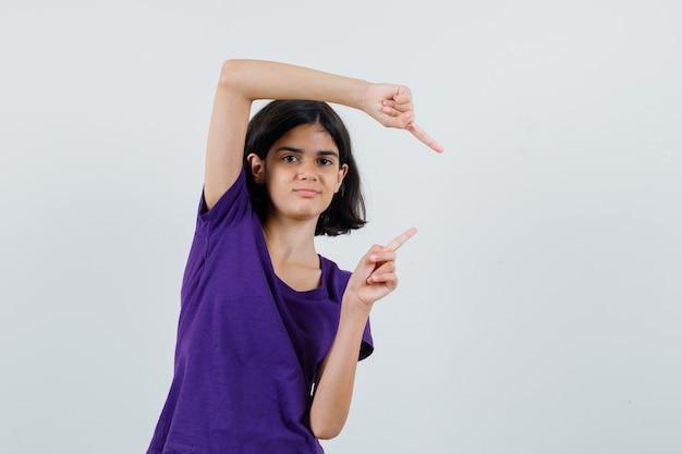 Meisje wijst naar de rechterkant in t-shirt en kijkt zelfverzekerd.