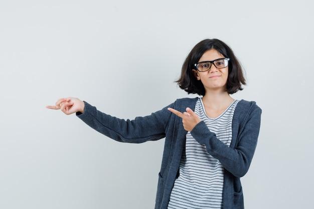 Meisje wijst naar de zijkant in t-shirt, jasje en kijkt zelfverzekerd