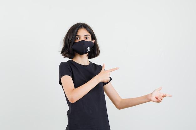 Meisje wijst naar de zijkant in zwart t-shirt, masker en kijkt nieuwsgierig. vooraanzicht.